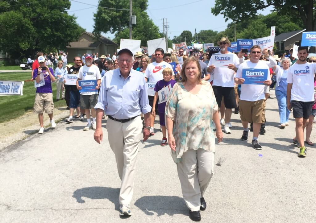 Sanders and wife Jane walk in the Waukee 4th of July parade